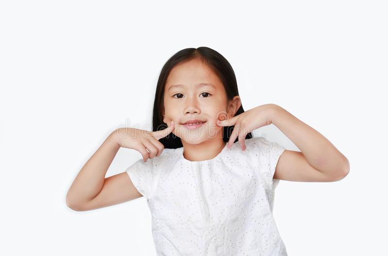 Smiling little Asian child girl holding two index fingers on her cheek isolated over white background royalty free stock image