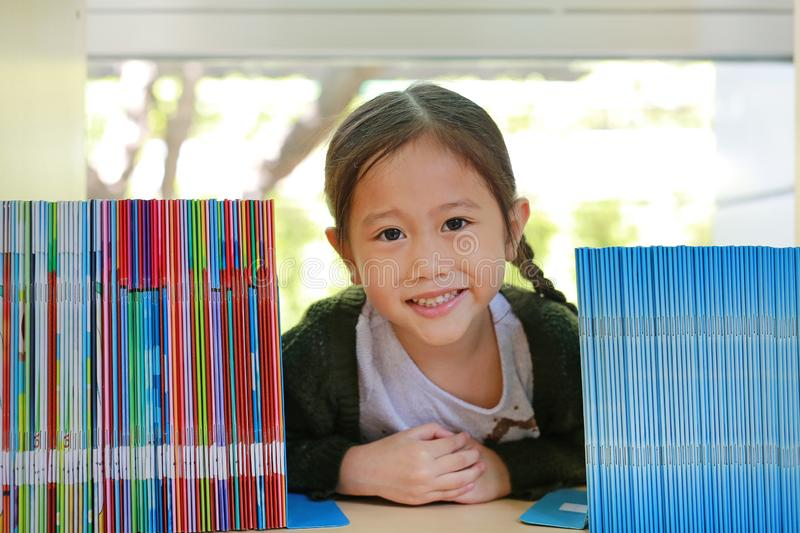 Smiling little Asian child girl lying on bookshelf at library. Children creativity and imagination concept.  stock photography