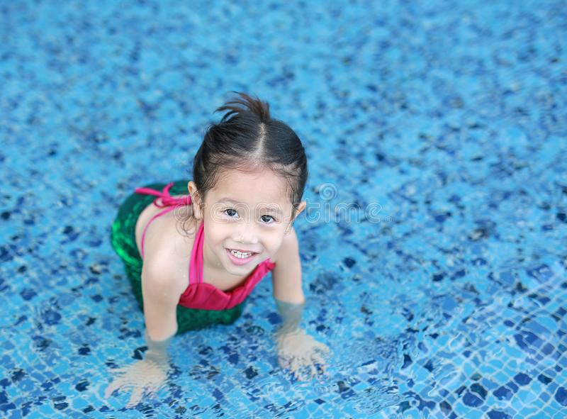 Smiling little Asian child girl in a mermaid suit playing poolside with looking camera.  stock photos