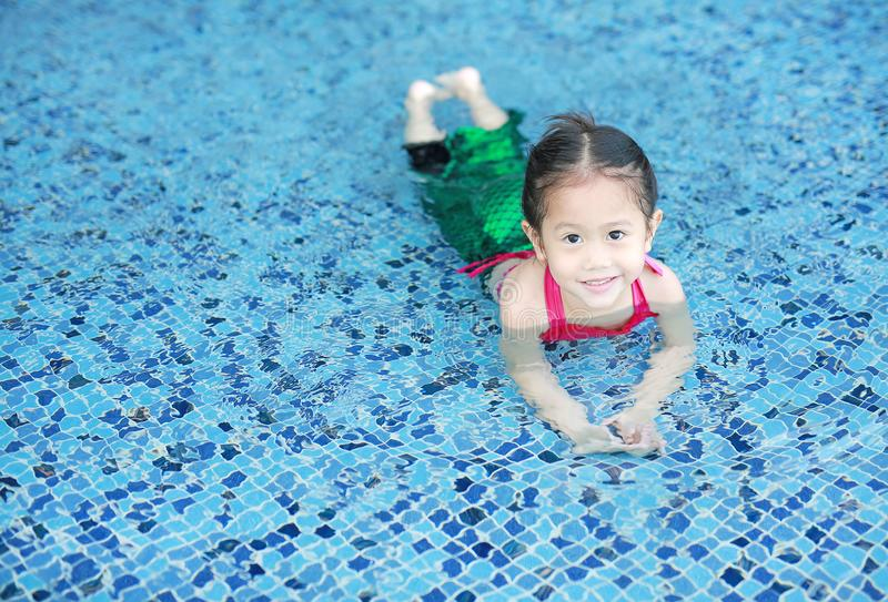 Smiling little Asian child girl in a mermaid suit playing poolside with looking camera.  royalty free stock photos