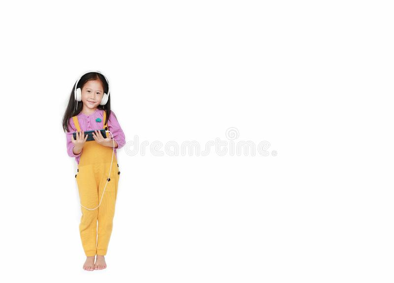Smiling little Asian child girl in pink-yellow dungarees with headphones to enjoys listening music by smartphone isolated on white royalty free stock photo