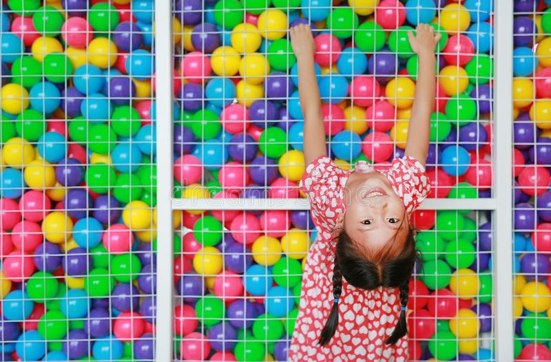 Smiling little Asian child girl playing climb and hanging on cage of playground colorful toy ball with looking camera stock photography