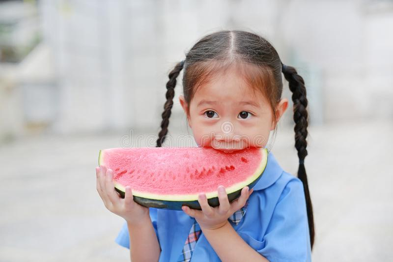 Smiling little Asian child girl in school uniform enjoy eating watermelon outdoors stock photography