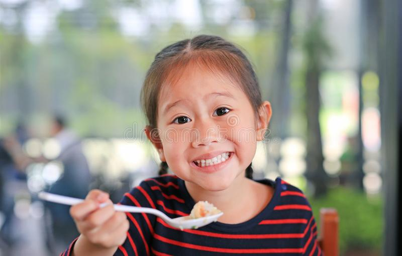 Smiling little Asian child girl sitting at the cafe and eating breakfast with looking straight at camera royalty free stock photography