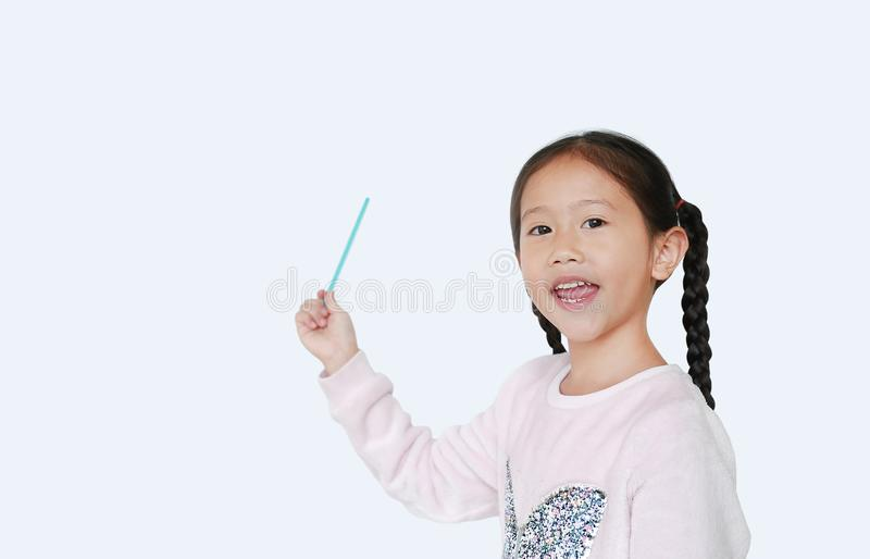 Smiling little Asian child girl standing and pointing up present something isolated over white background. Asian schoolgirl in stock image