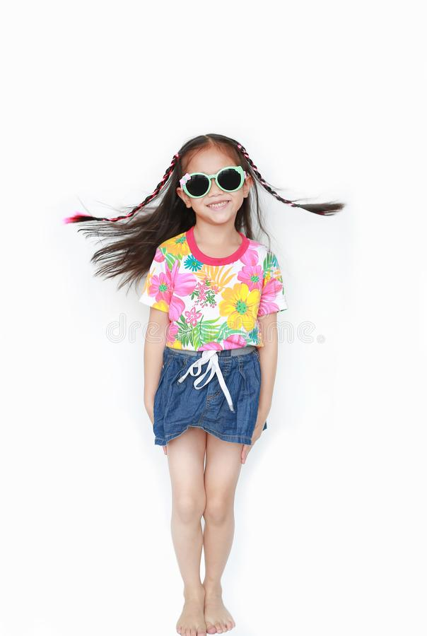 Smiling little Asian child girl wearing a floral pattern summer dress and sunglasses isolated on white background. Summer and stock image
