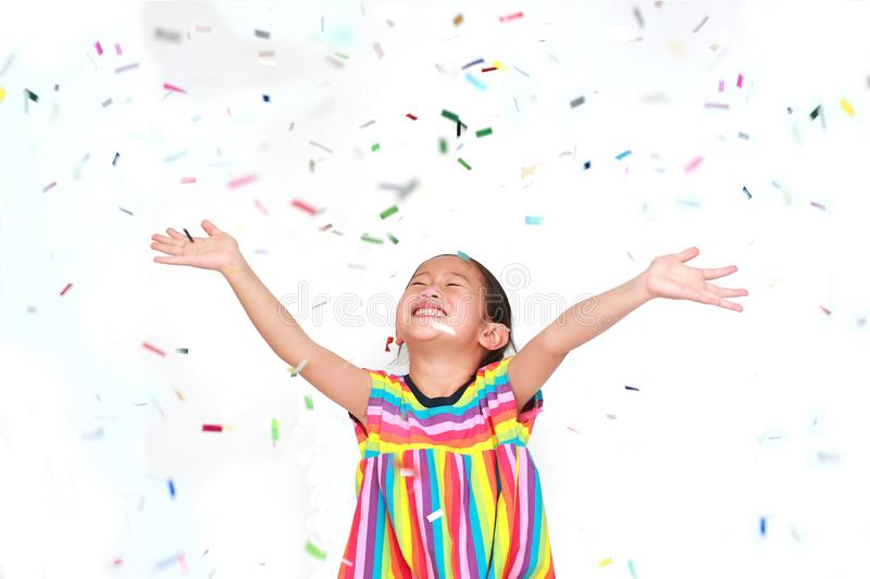 Smiling little Asian kid girl with many falling colorful tiny confetti pieces on white background. Happy New Year or. Congratulation Concept stock image