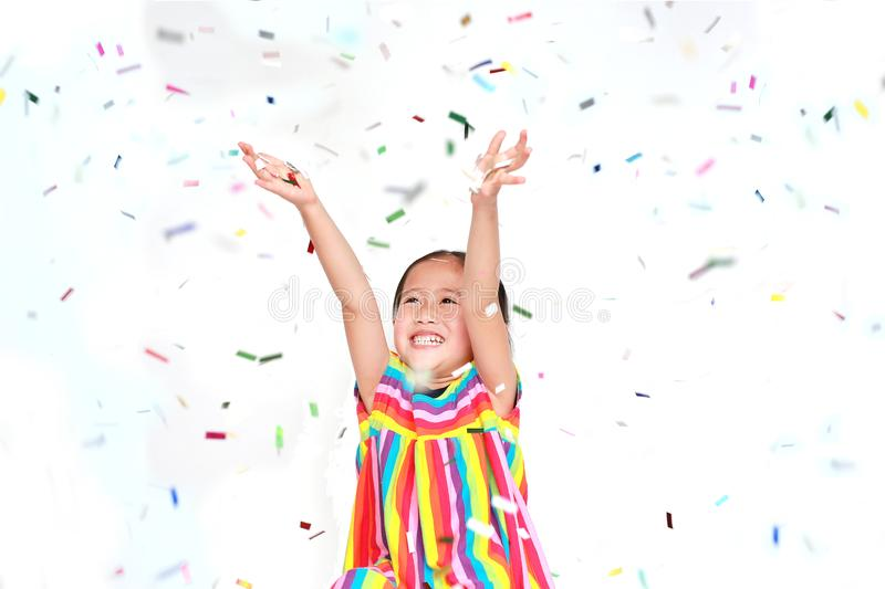 Smiling little Asian kid girl with many falling colorful tiny confetti pieces on white background. Happy New Year or. Congratulation Concept stock photo