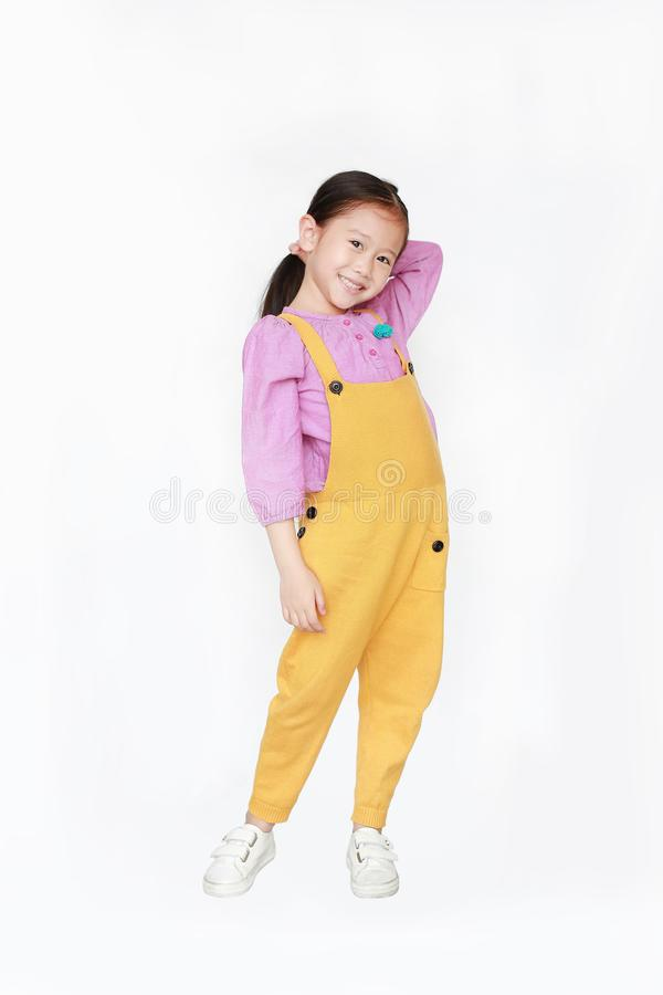 Smiling little Asian kid girl in pink-yellow dungarees poses touched hair keep back isolated on white background. Full length of royalty free stock images