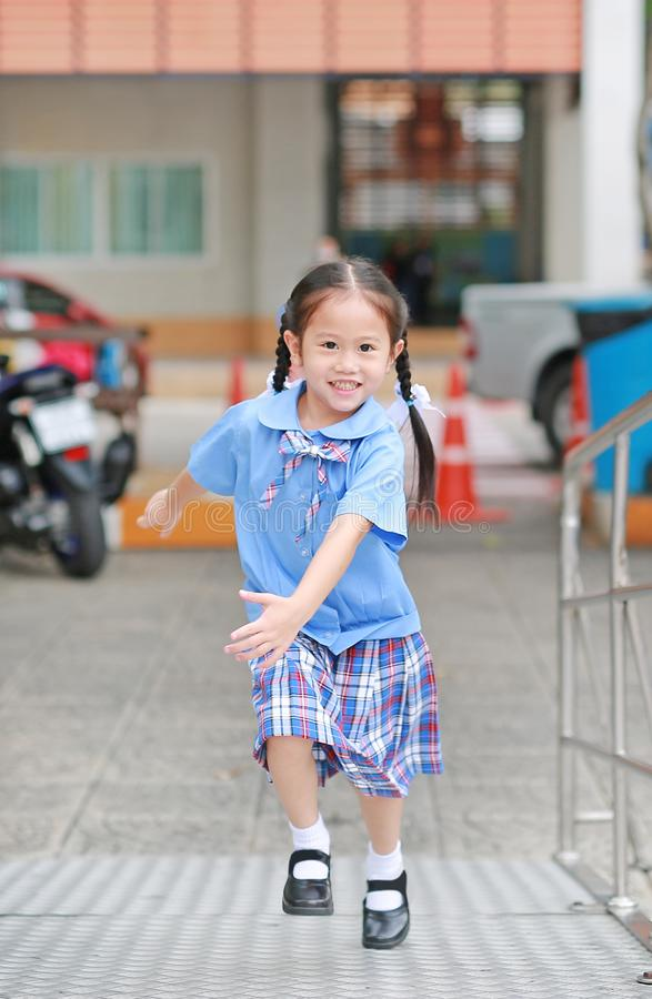 Smiling little Asian kid girl in school uniform running up metal stair.  stock photography