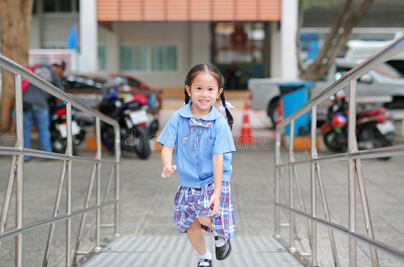 Smiling little Asian kid girl in school uniform running up metal stair stock image