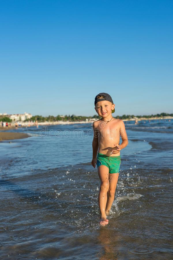 Smiling little baby boy running with splash in the sea on the beach at sunset. Portrait of happy little kid boy on the beach of stock photos