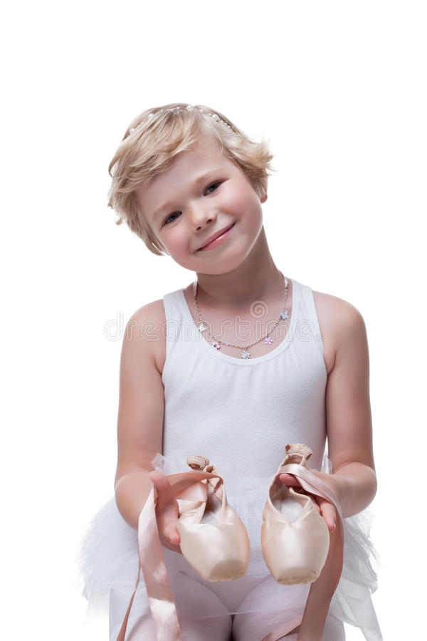Smiling little blonde posing with pointe shoes royalty free stock photography