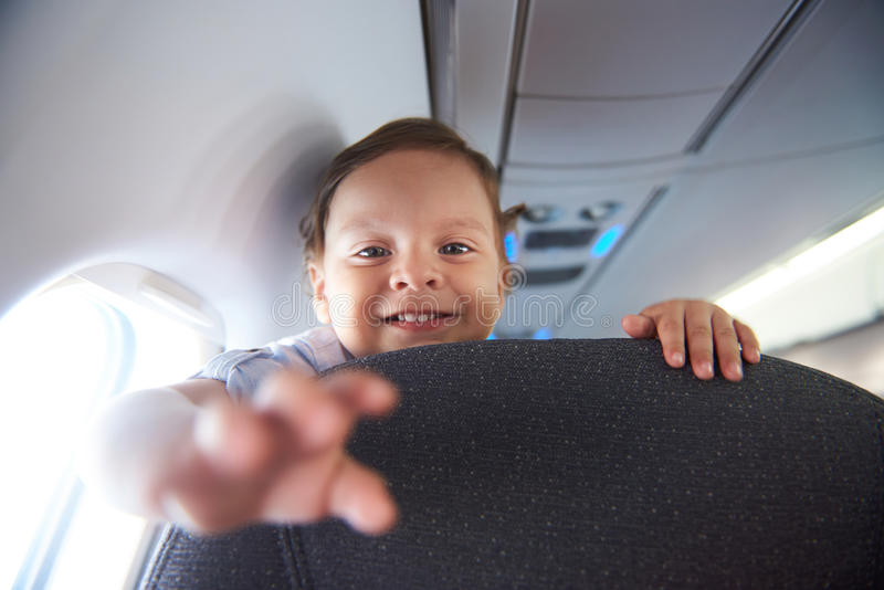 Smiling little boy in airlane. Smiling little boy travel in airlane. Child air plane passenger royalty free stock photo