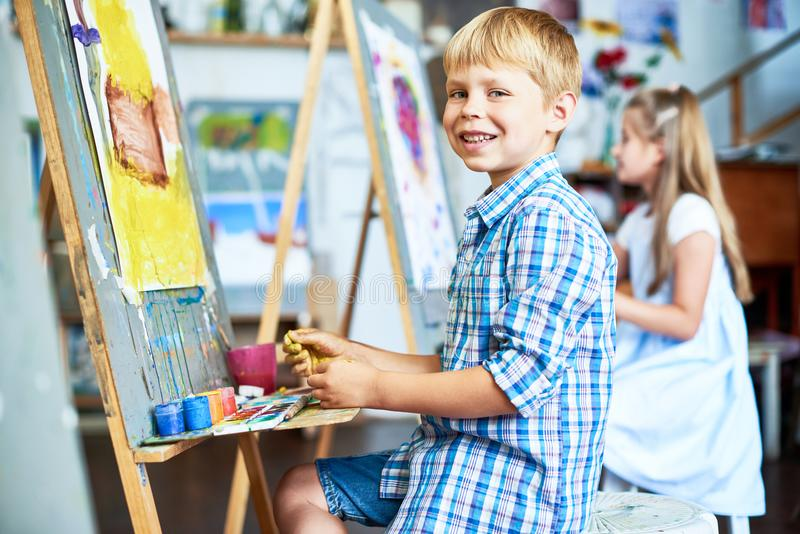 Smiling Little Boy in Art Class. Side view portrait of little boy fingerpainting house on easel in art studio and looking at camera smiling happily stock photo
