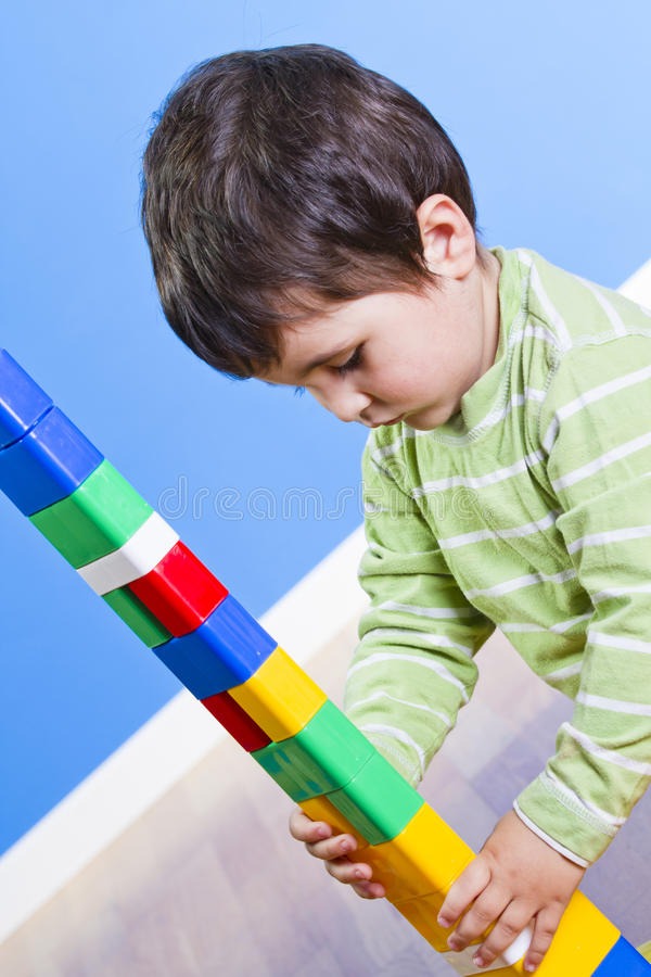 Building Toys For Little Boys : A smiling little boy is building toy block stock photo