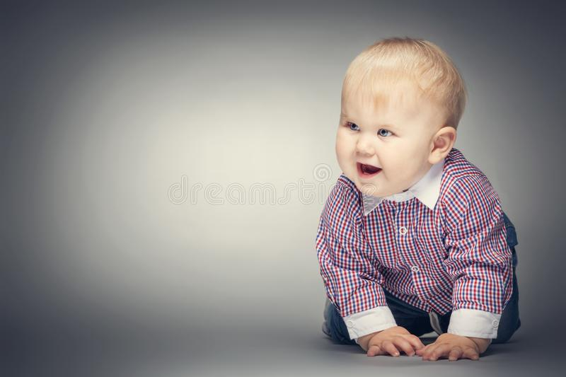 Smiling little boy crawling on the ground. stock image