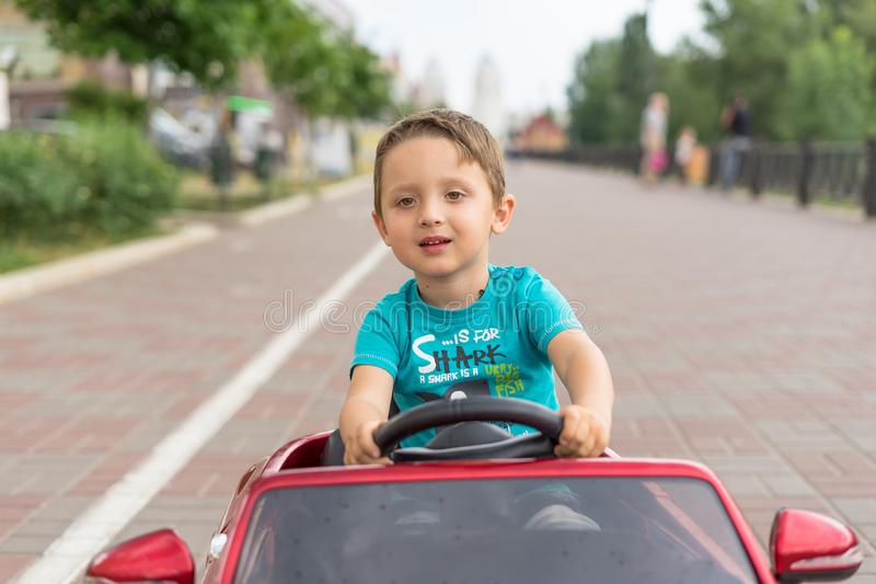 Smiling little boy driving by toy car. Active leisure and sports for kids. Portrait of happy little kid on the street. Funny cute stock images