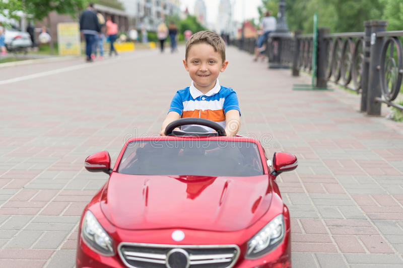 Smiling little boy driving by toy car. Active leisure and sports for kids. Portrait of happy little kid on the street. Funny cute royalty free stock photography