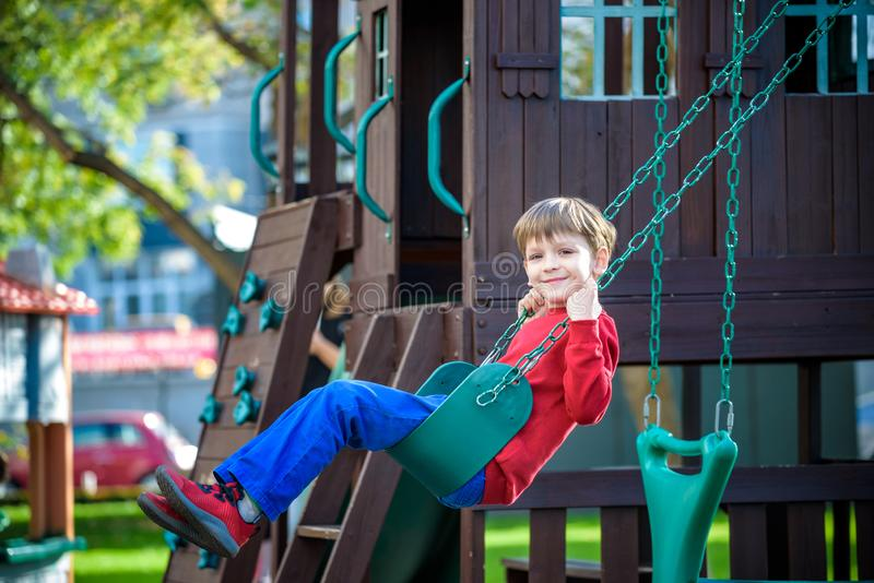 Smiling little boy and his brother friend on a swing. Children p royalty free stock photo