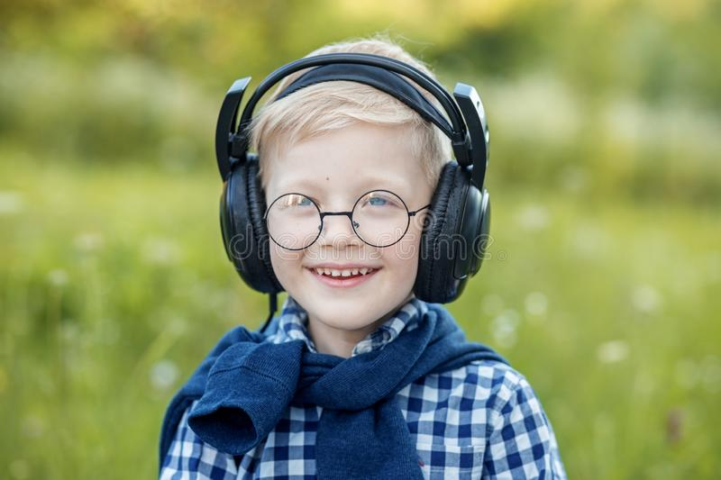 A smiling little boy listens to the radio with headphones. The concept of music, study and lifestyle. A smiling little boy listens to the radio with headphones stock images