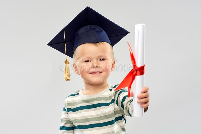 Smiling little boy in mortar board with diploma stock photography