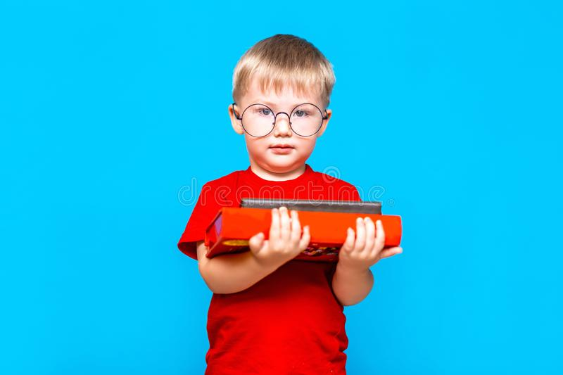 Smiling Little boy in round glasses holding a stack of books. education. ready to school.  stock images