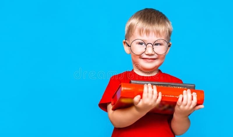 Smiling Little boy in round glasses holding a stack of books. education. ready to school.  stock photo