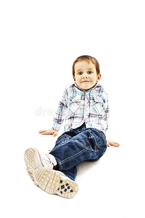 Smiling little boy sitting down on floor. And looking at camera. Isolated on white background royalty free stock images