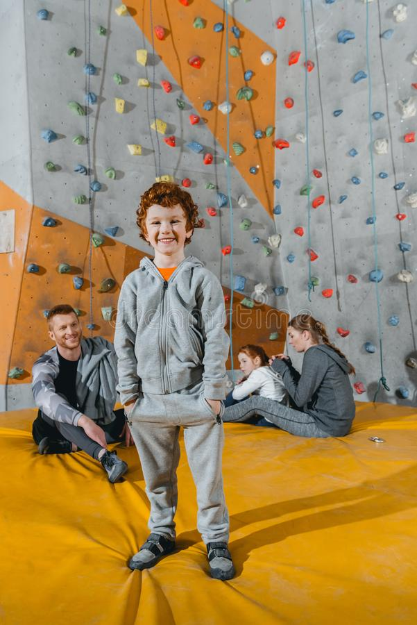 Smiling little boy in sportive attire standing in front of a climbing wall and looking. At camera stock image