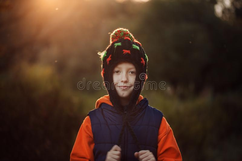 Smiling little boy in warm hat in sunny autumn day. royalty free stock photography