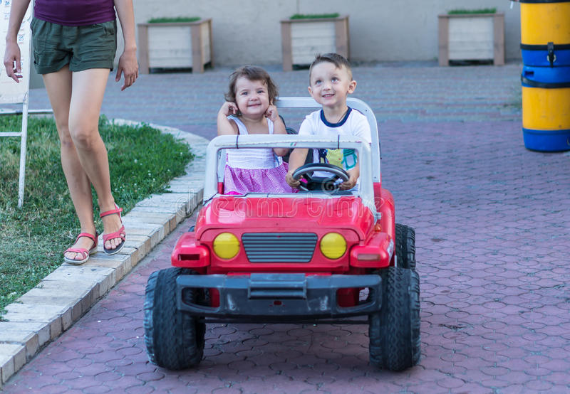 Smiling little brother and sister driving by toy car. Portrait of happy little kids on the street. Funny cute children making vaca stock photography