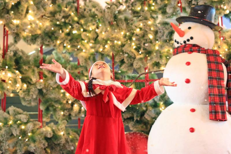Smiling little child girl in santa costume dress play with snow on winter time against christmas background. Merry Christmas and. Happy new year stock image