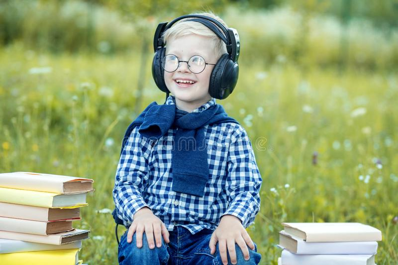 A smiling little child listens to songs in headphones. The concept of music, study, and lifestyle royalty free stock photos