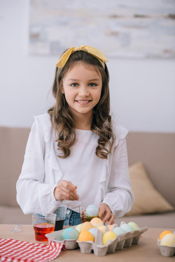 smiling little child painting easter eggs and looking royalty free stock photography