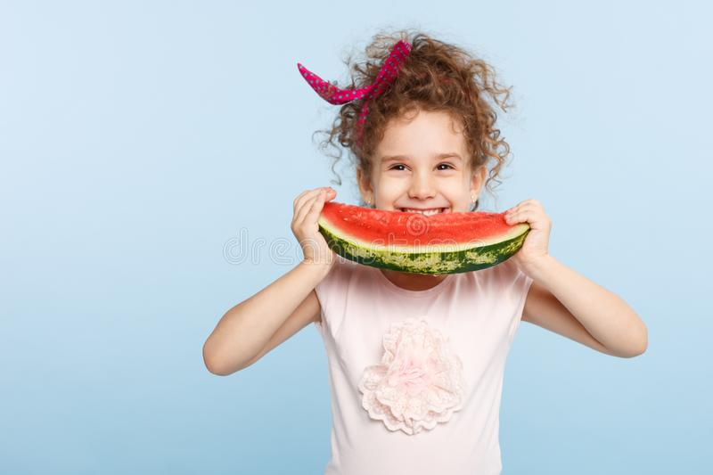 Smiling little curly girl holding with hands a large slice of watermelon, try to bite, isolated on a blue background. stock image