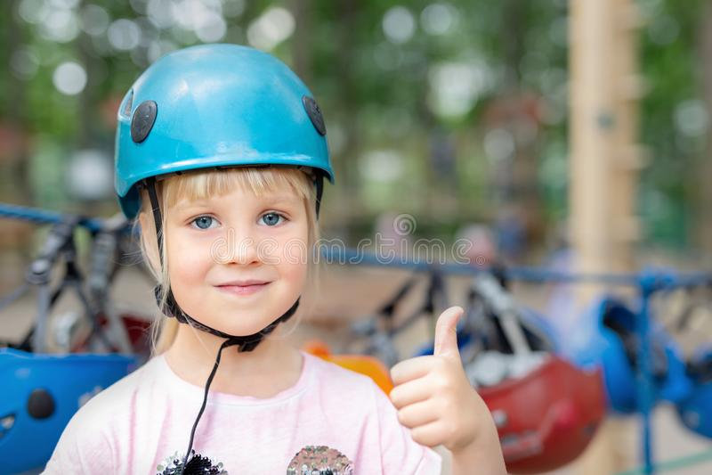 Smiling little cute blond caucasian girl in helmet showing thumbs up. Safety accessories of extreme entertainment on background. A stock photography
