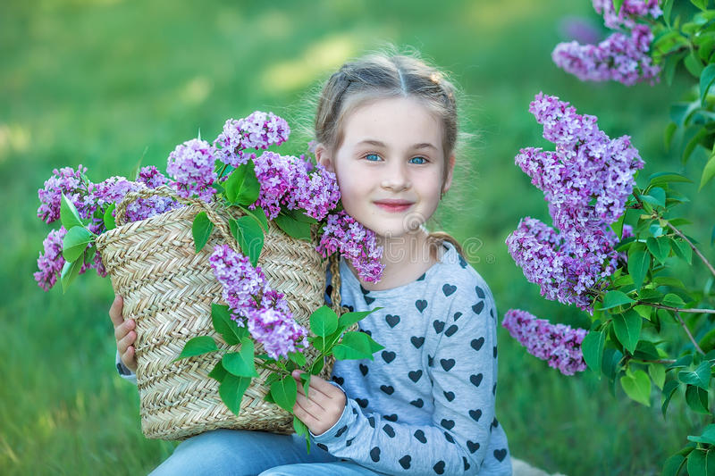 Smiling little cute blonde child girl 4-9 years with a bouquet of lilac in the hands in jeans and shirt royalty free stock image