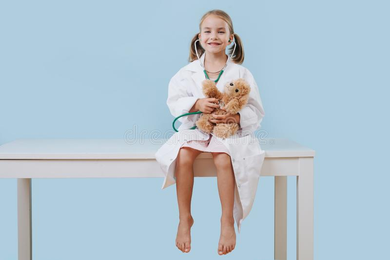 Smiling little girl playing doctor, wearing long white robes with stethoscope royalty free stock images