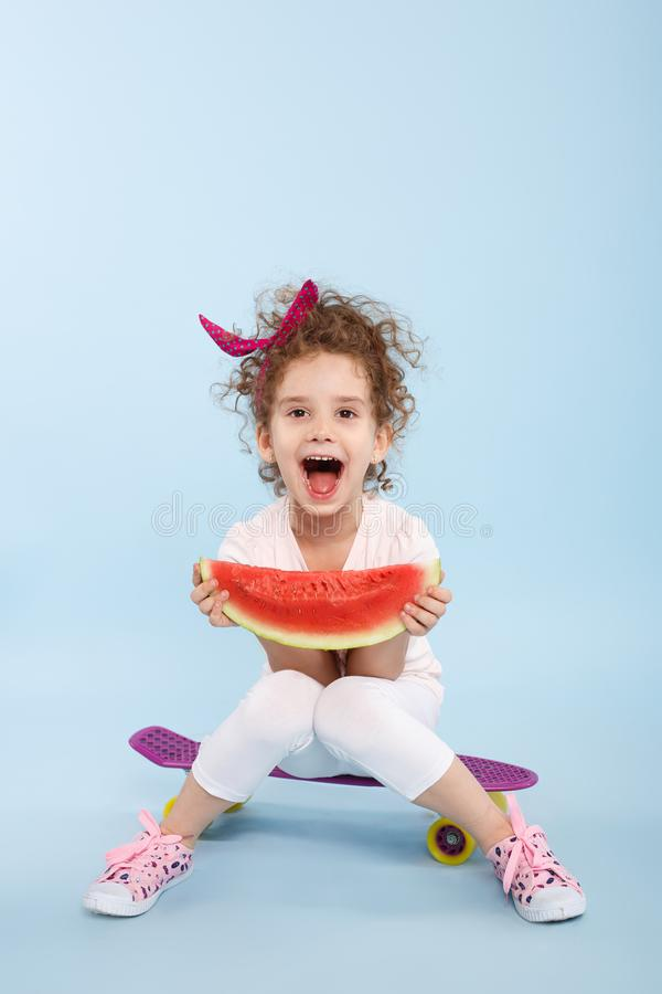 Portrait of little girl holding in hands a slice a watermelon, seated on a skateboards, isolated on a blue background. royalty free stock image