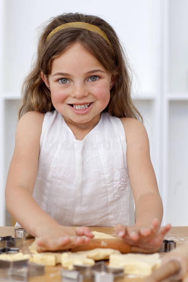 Smiling little girl baking in the kitchen. Smiling beautiful little girl baking in the kitchen stock image