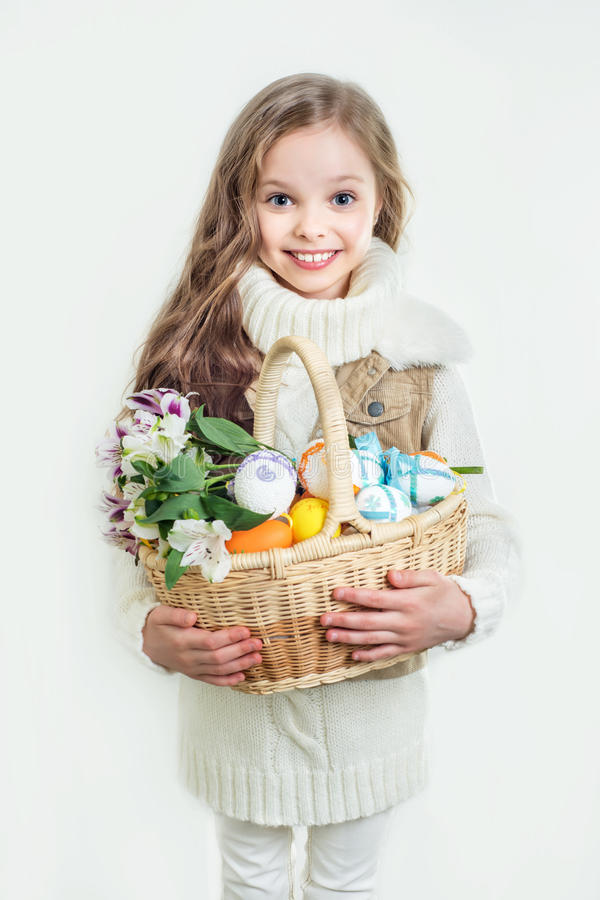 Smiling little girl with basket full of colorful easter eggs. And flowers. Easter. Spring stock photography