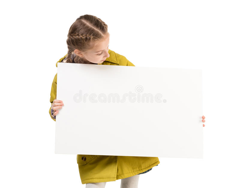 Smiling little girl with blank sheet in hands. Smiling little girl in coat with blank sheet in hands isolated on white background stock image