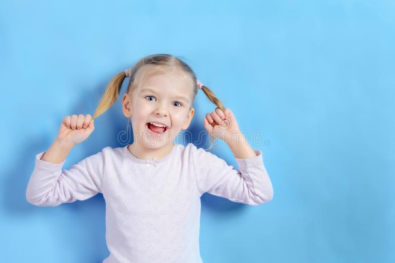 Smiling little girl with blond hair on a blue background. The child holds and pulls tails on his head in different. Directions. Bright photo with bright emotion stock photography