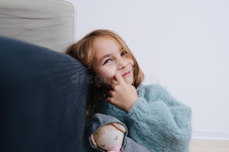 Smiling little girl in a blue sweater with rag doll sitting on the floor royalty free stock image