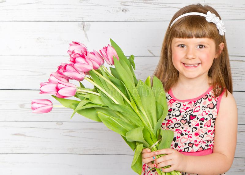 Smiling little girl with a bouquet of pink tulips in her hand stock image