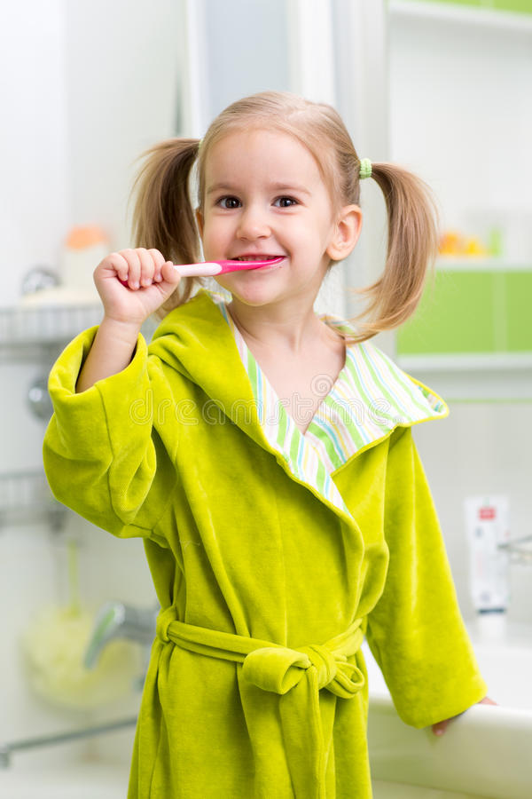 Smiling little girl brushing teeth in bath royalty free stock images