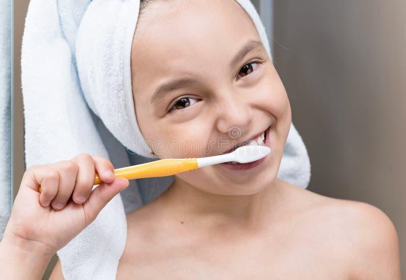 Smiling little girl brushing teeth stock images