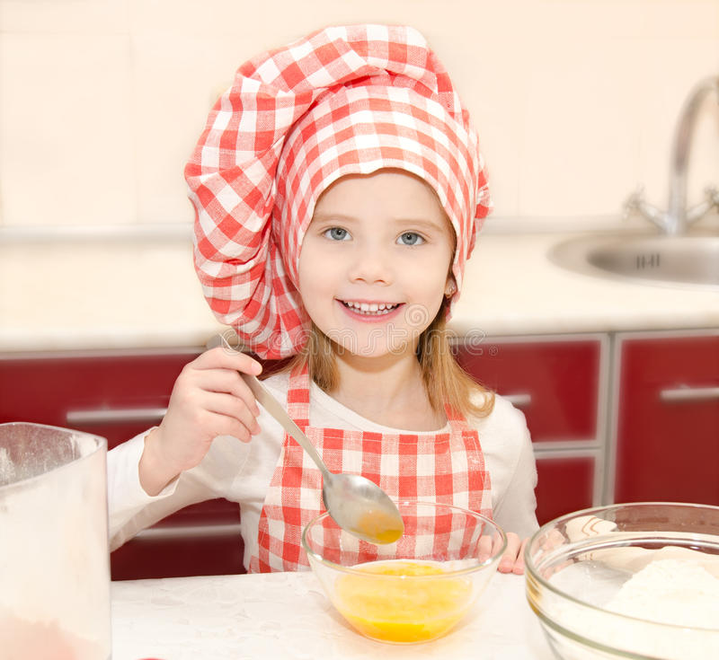 Smiling little girl with chef hat stirrring cookie dough. In the kitchen royalty free stock photo