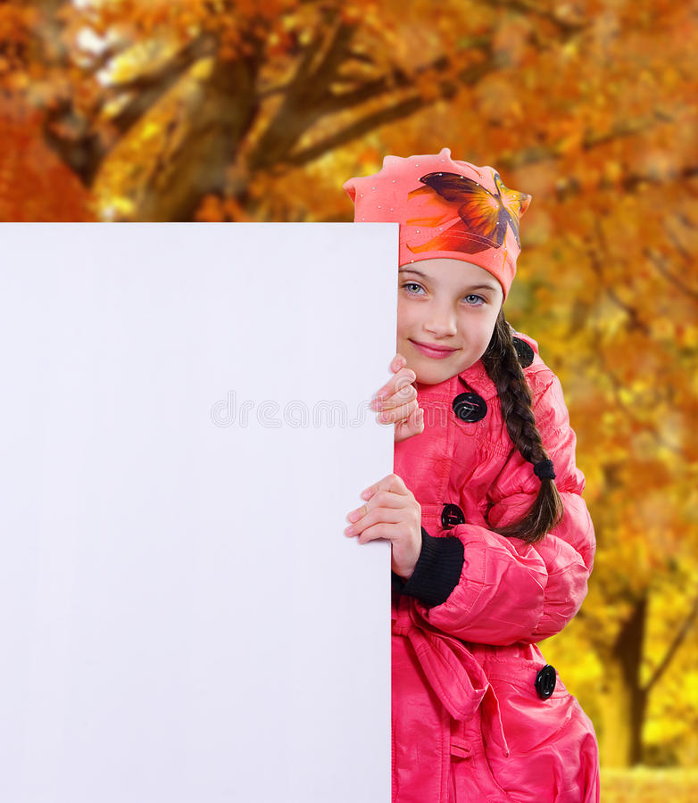 Smiling little girl child in autumn clothes jacket coat and hat holding a blank billboard banner white board. Smiling little girl child in autumn clothes jacket stock image